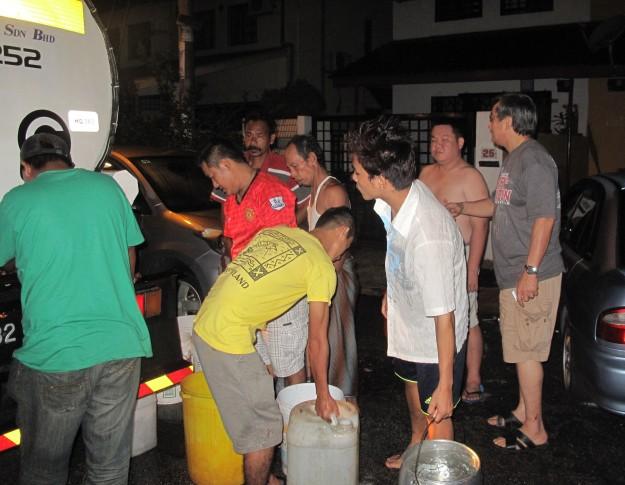 Penduduk-penduduk menunggu mengambil air