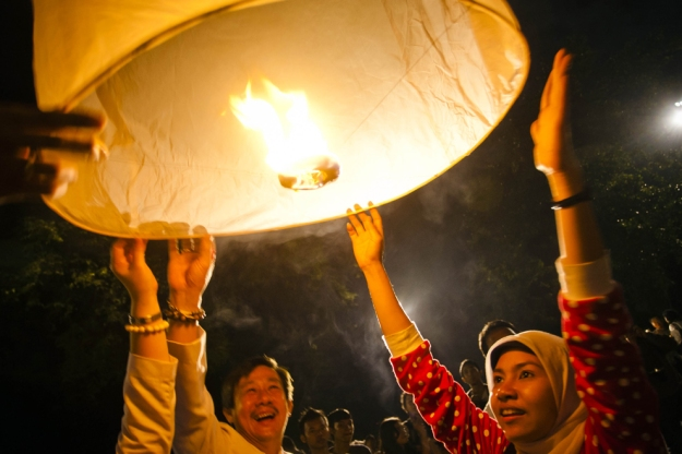 Indonesian muslim woman with Buddhist followers release a lantern into the air at the Borobudur temple during Vesak Day, commonly known as 'Buddha's birthday', at the Borobudur Mahayana Buddhist monument on May 17 in Magelang, Indonesia. Buddhists in Indonesia celebrate Vesak at the monument anually, which makes it the most visited tourist attraction in Indonesia. It is observed during the full moon in May or June, with the ceremony centred at three Buddhist temples by walking from Mendut to Pawon and ending at Borobudur. (Ulet Ifansasti/Getty Images)